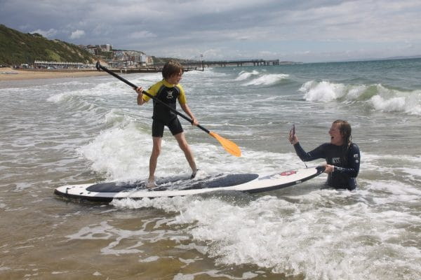 Mum taking photo of son on paddle board